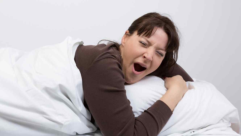 Mujer con blusa café acostada en una cama y bostezando