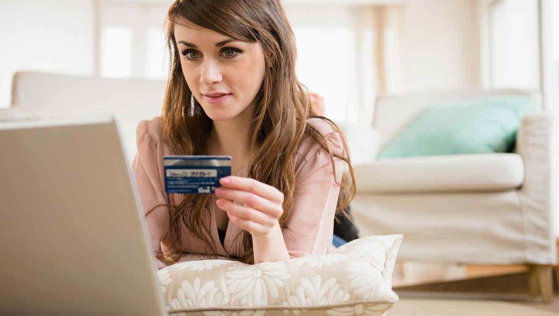 Mujer joven paga con tarjeta por Internet