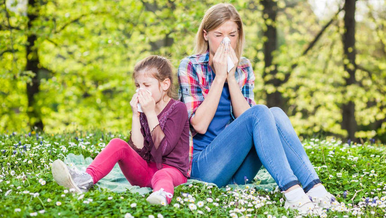 Madre e hija sentadas en el césped sacudiéndose la nariz