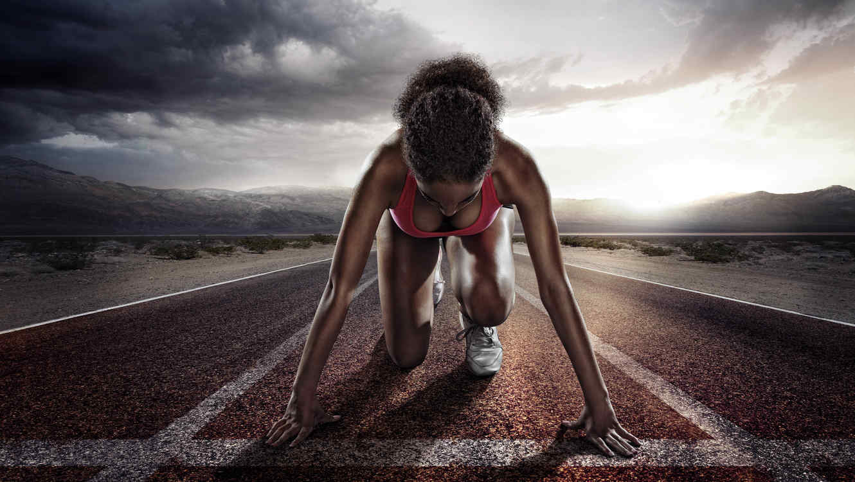 Mujer atleta sobre la pista lista para correr
