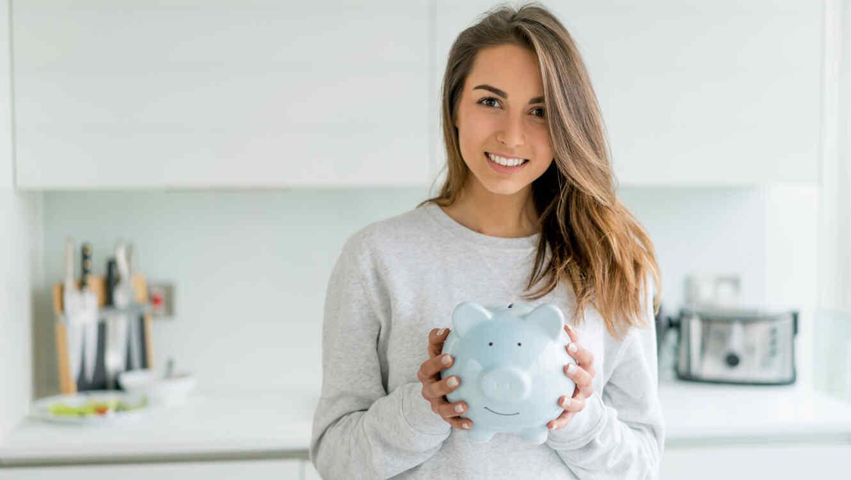 Mujer joven con un cerdito para ahorros