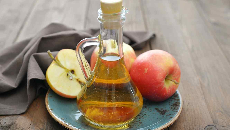 Botella con vinagre junto a unas manzanas
