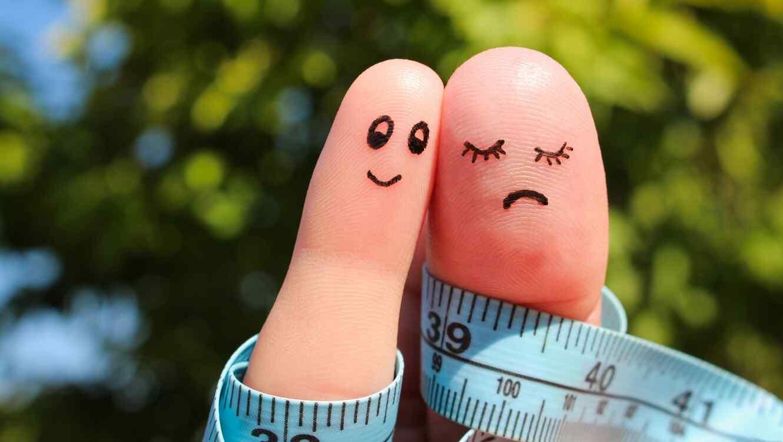 Dos dedos con rostros dibujados y enredados con cinta de medir
