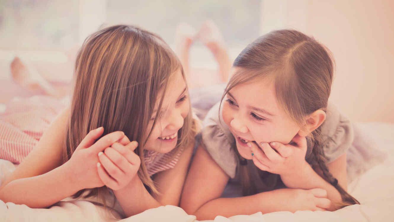 Hermanas bromeando en la cama