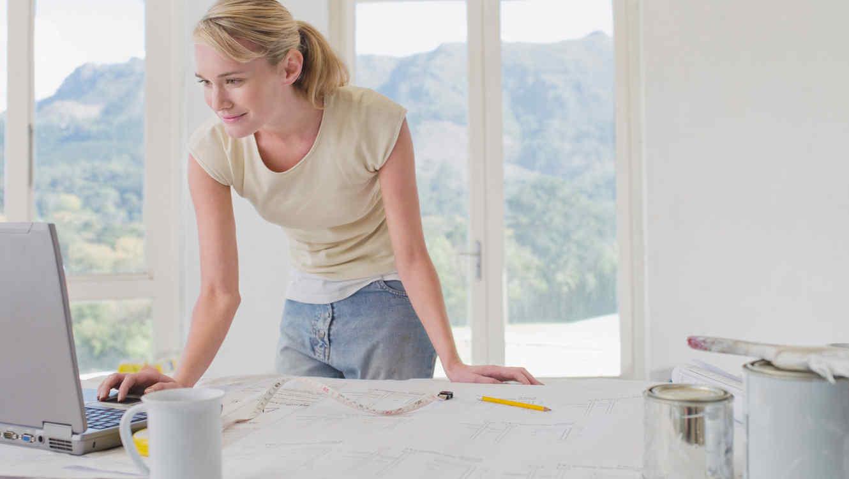 Mujer pinta la casa y checa computadora