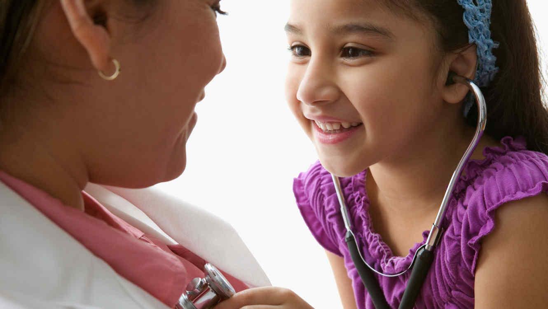 Niña latina revisa a médica con estetoscopio