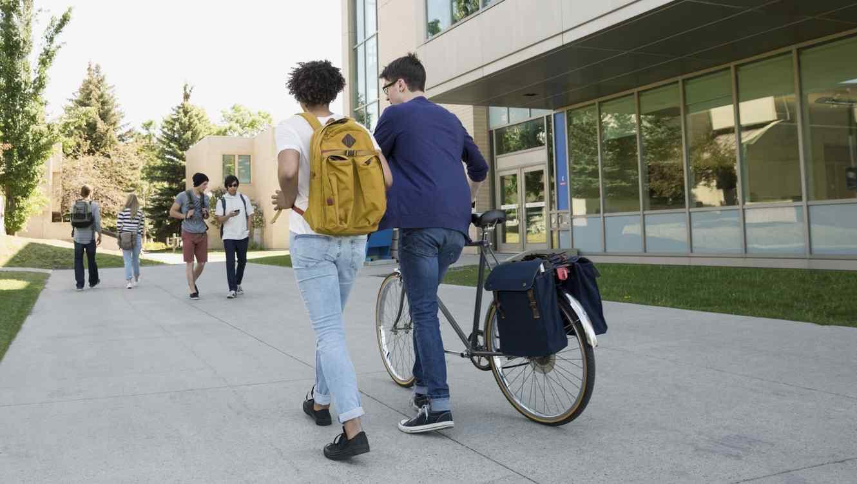 Jóvenes con bicicleta en campus