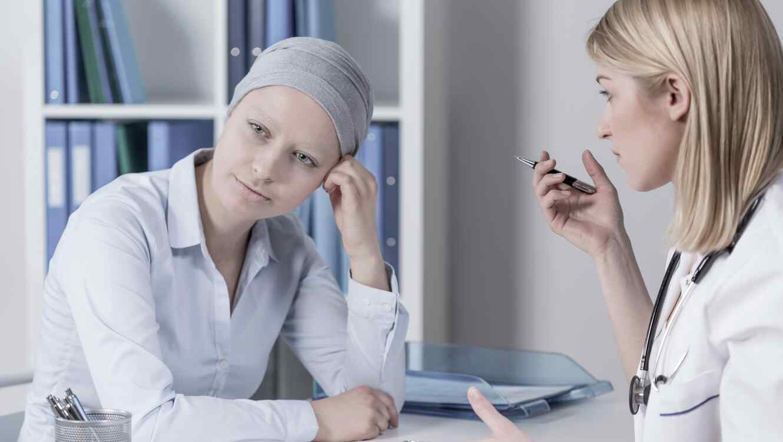 Mujer con pañuelo en la cabeza junto a una médica