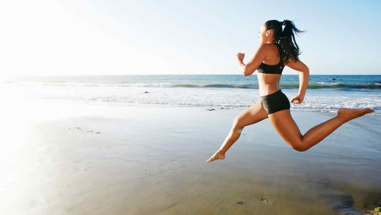 Mujer corriendo descalza en la playa