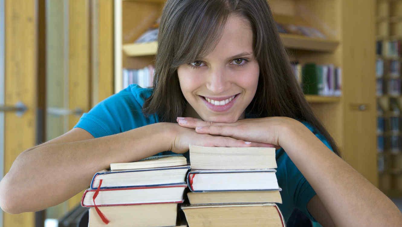 Chica joven sonríe con pila de libros