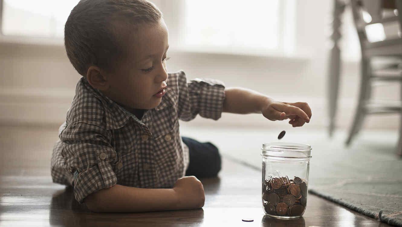 nio juega en el piso con monedas