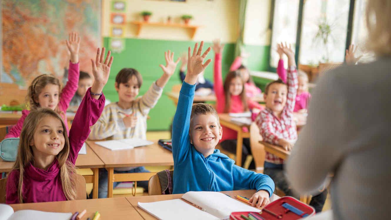 Niños con las manos levantadas listos para responder