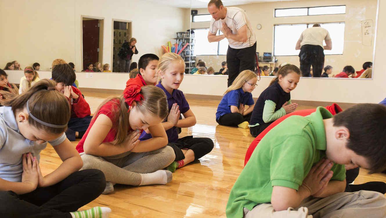 Niños meditando en clase de gimnasia