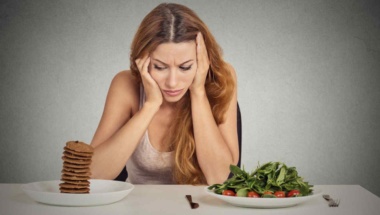 Mujer con indecisión frente a dos tipos de comida