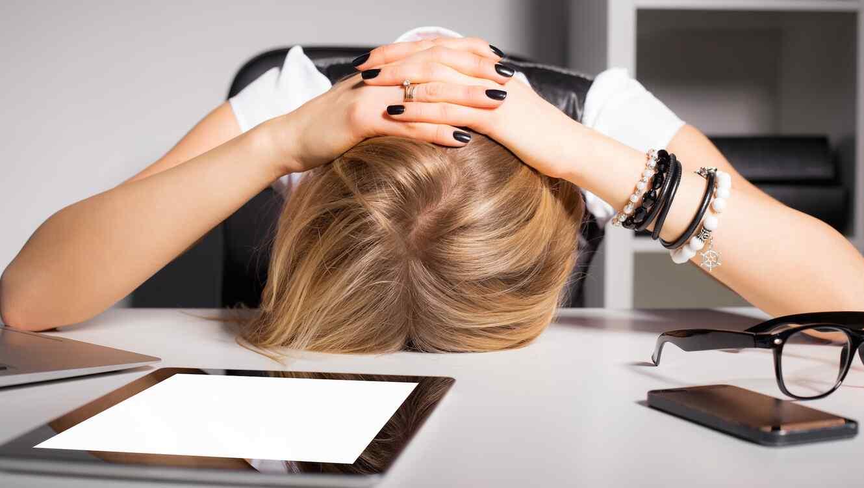 Mujer con la cabeza apoyada sobre su escritorio