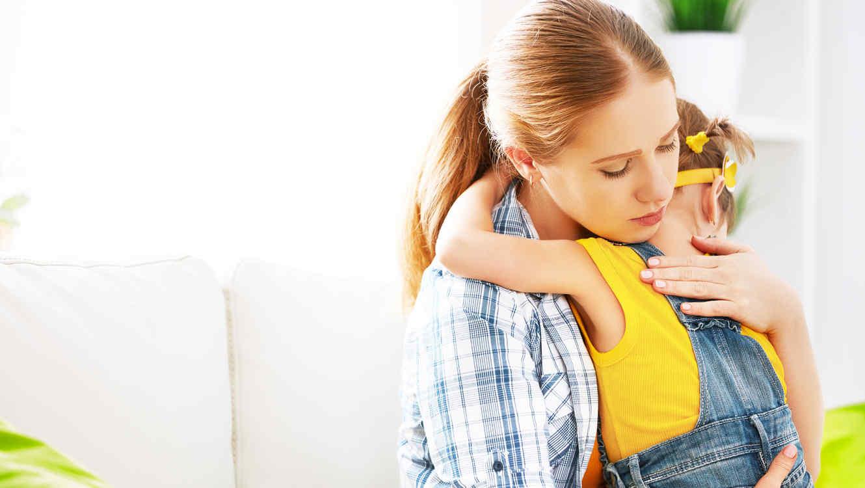 Niña de espalda abrazando a su mama