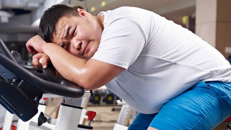 Hombre joven obeso cansado en bicicleta fija