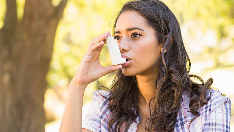 Mujer morena al aire libre usando un bronqueo dilatador