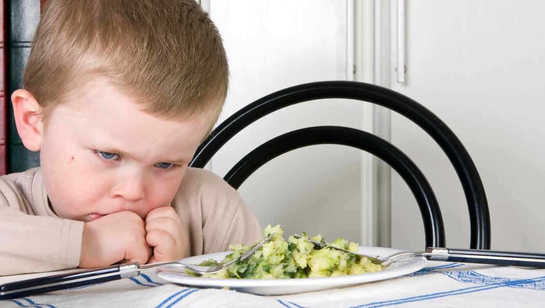 Niño pequeño negándose a comer vegetales