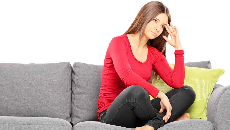 Mujer preocupada sentada en sofá