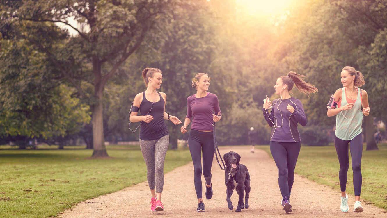 Mujeres corriendo en el parque con un perro