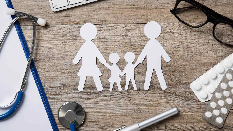 Recorte de familia en papel con elementos médicos alrededor