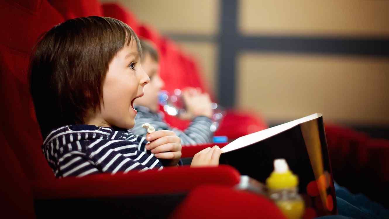 Niño pequeño con palomitas de maíz en el cine