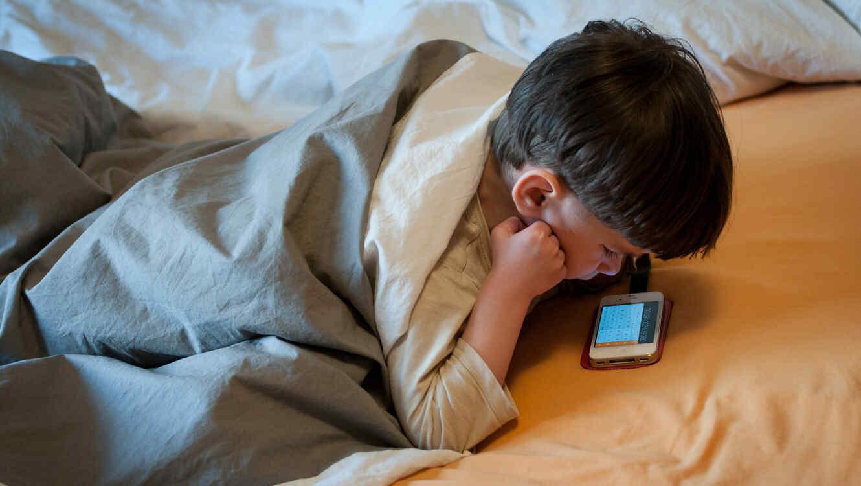 Niño usando el celular en la cama