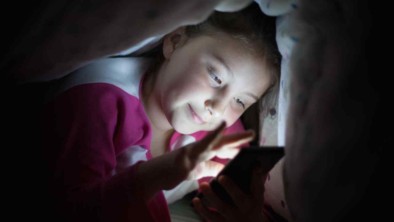Niña usando teléfono móvil a escondidas
