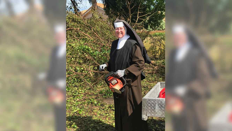 La hermana Margaret Ann de la preparatoria Archbishop Coleman F. Carroll usando una sierra para cortar un árbol caído después del paso del huracán Irma.
