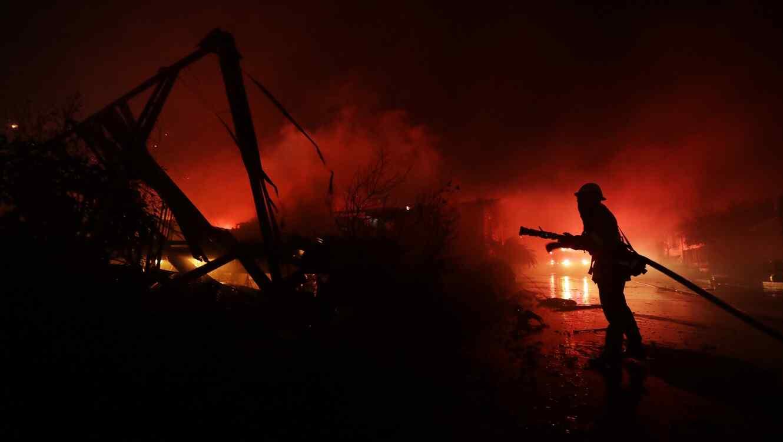 Los bomberos trabajan entre las casas destruidas en Fallbrook, California.