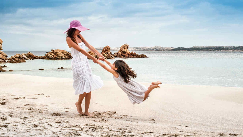 Mamá e hija jugando en la playa
