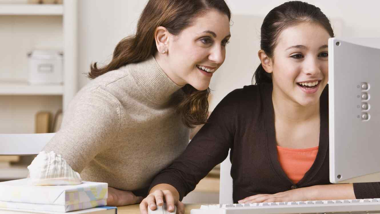 Hija adolescente y madre usando computadora juntas