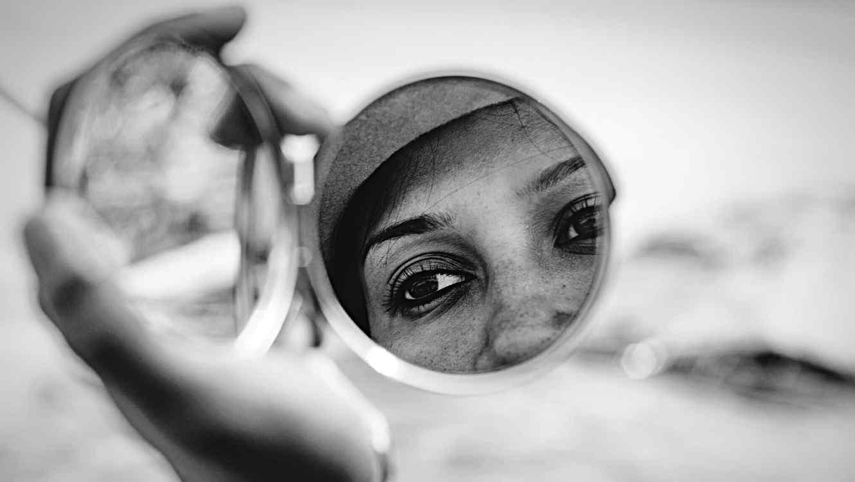 Mujer mirándose en un espejo compacto