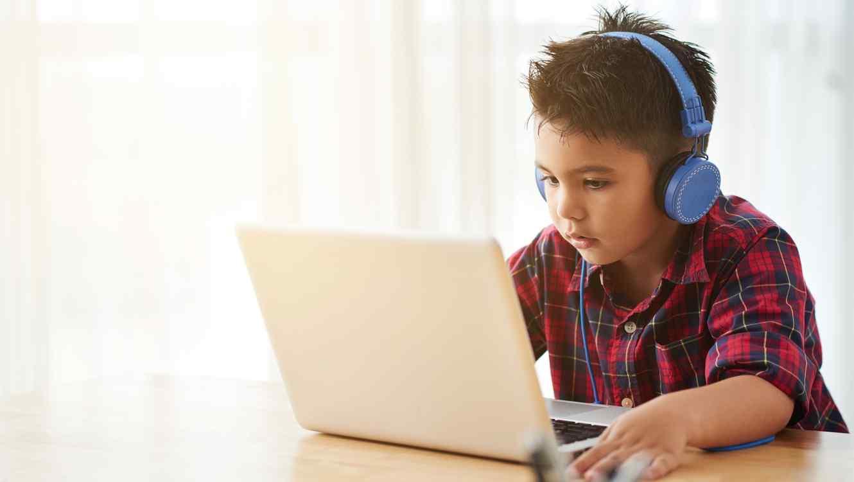 Niño con auriculares usando computadora