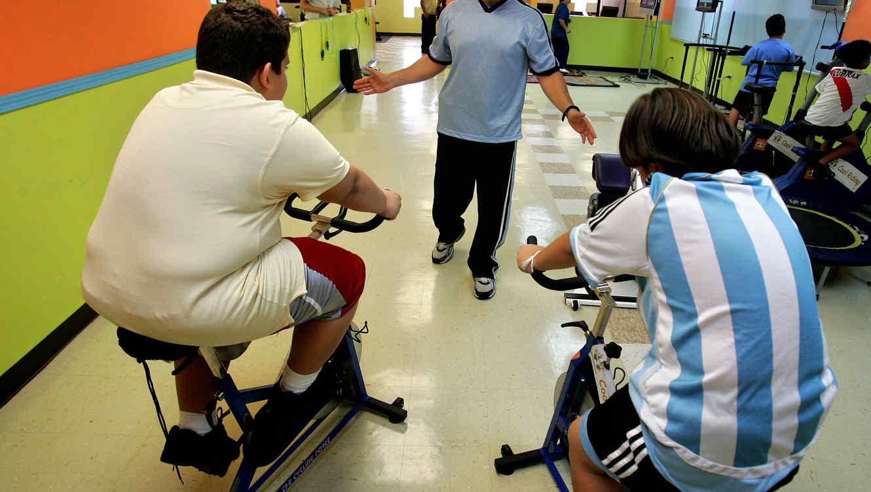 Niños con sobrepeso realizan ejercicios en un gimnasio en una imagen de archivo
