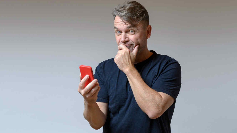 Hombre confundido sosteniendo un celular