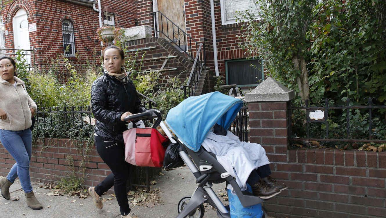 Dos mujeres cruzan por delante de la vivienda de Jakiw Palij en Nueva York en noviembre de 2017, durante una protesta para forzar a las autoridades a deportarlo.