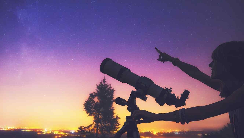 Mujer con telescopio señalando el cielo nocturno