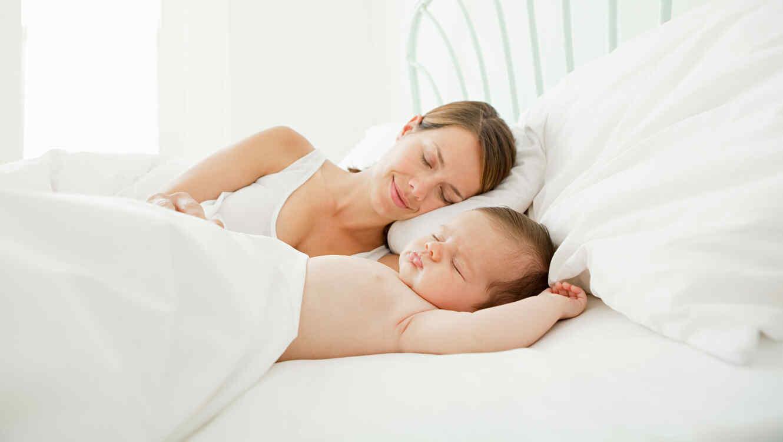 Mamá durmiendo con su bebé recién nacido