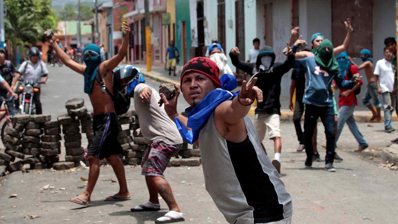 Manifestantes tiran piedras contra la policía durante una protesta contra el gobierno del presidente de Nicaragua, Daniel Ortega, en Nomimbo (12 de mayo de 2018)