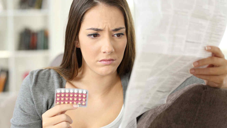 Mujer leyendo el prospecto de las píldoras anticonceptivas