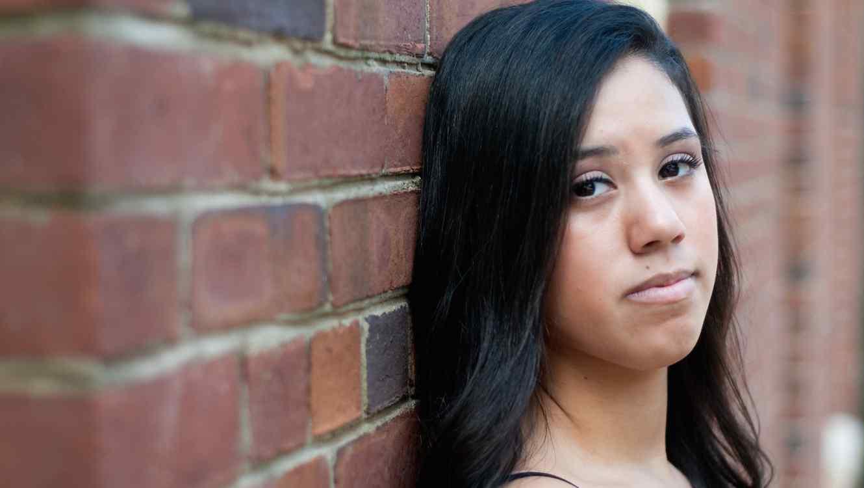 Niña latina triste contra muro