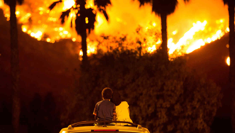 Dos niños miran desde el techo de un carro uno de las decenas de incendios que arden en California