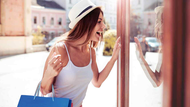 Mujer con bolsas observando vidriera
