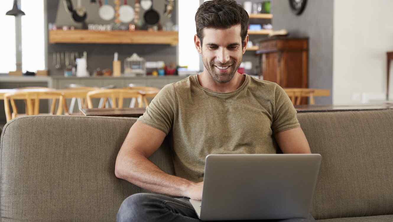 Hombre usando computadora en el sofá de su casa