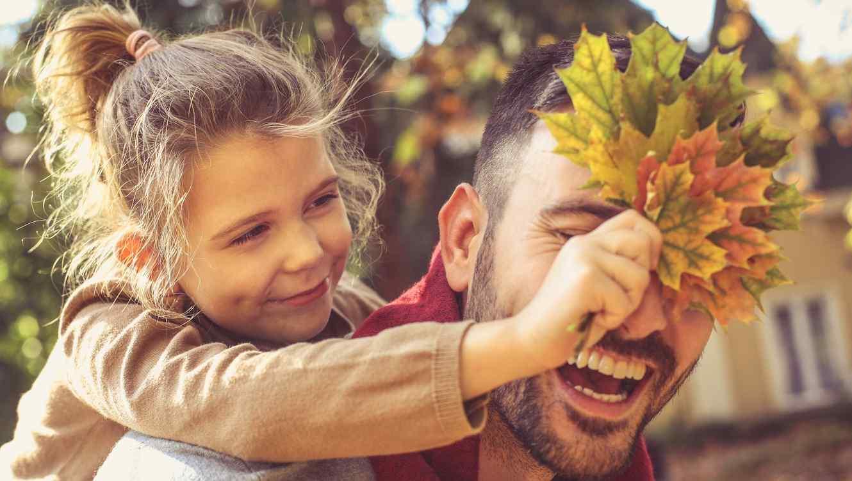 Niña y padre jugando con hojas de otoño