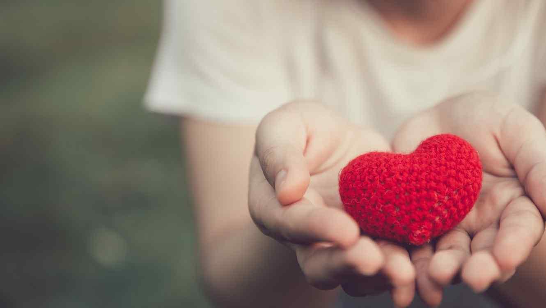 Mujer sosteniendo corazón tejido