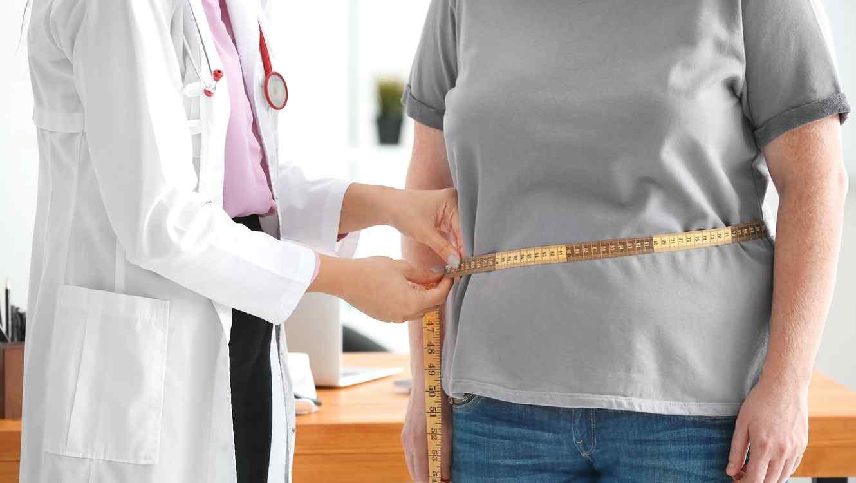 Médica midiendo la cintura de paciente