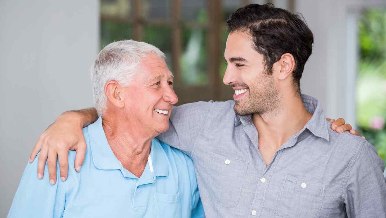 Hombre mayor junto a su hijo adulto